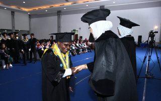 Demi Nawipa ontvangt de felicitaties van de examencommissie voor zijn afstuderen als geoloog