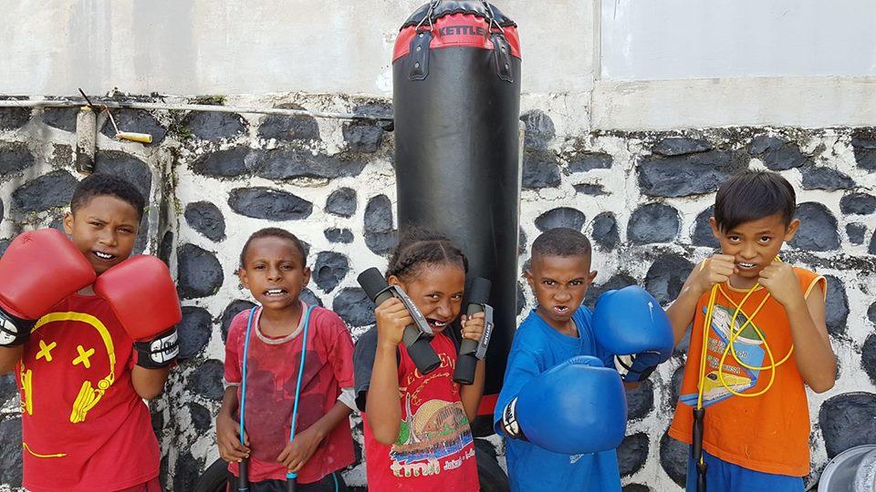 Trots laten deze kinderen de materialen zien die konden worden gekocht van de bijdrage van Hapin